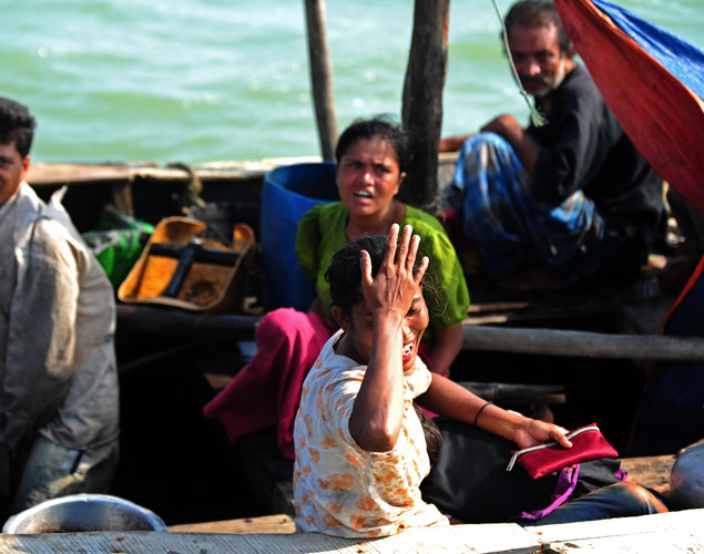 A Rohingya Muslim woman, fleeing sectarian violence, cries on an intercepted boat as they try to cross the Naf river into Bangladesh in Teknaf.