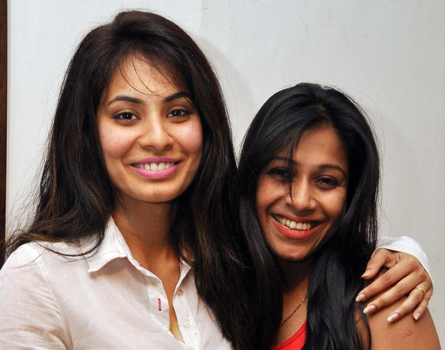 Manisha Kelkar (L) and singer Annie Chaterjee (R) pose for a photo during a painting exhibition promoting her upcoming film Bandook in Mumbai.