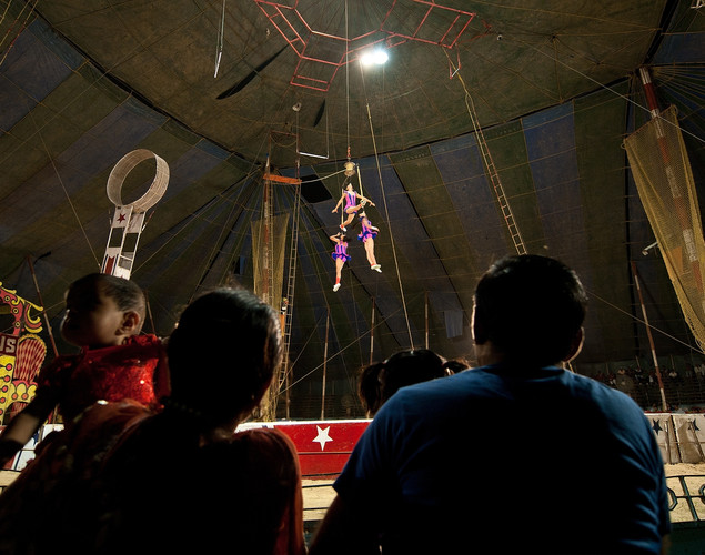An Indian family watches as trapeze artists perform at the Jumbo Circus in Gurgaon.
