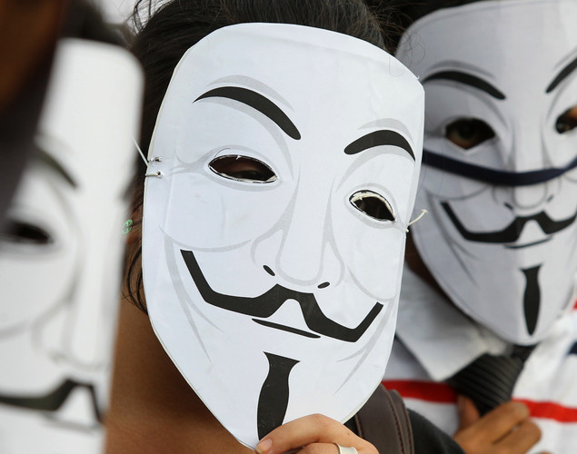 Activists supporting the group Anonymous wear masks as they protest against the Indian Government's increasingly restrictive regulation of the internet outside a shopping mall in Bangalore.