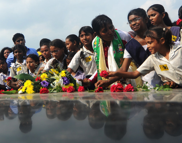 Bangladeshi mountaineer Wasfia Nazreen (3R) places a rose on the Martyred for Intellectuals Memorial in Dhaka.