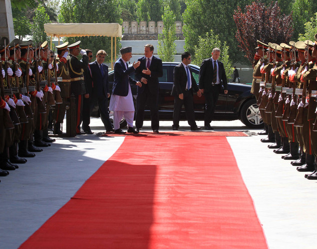 Afghan President Hamid Karzai (L) greets Britain's Prime Minister David Cameron (C) during a guard of honour ceremony in Kabul.