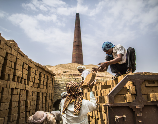 Laborers stack bricks to be baked as a 'Chai Wallah' or Tea Man serves tea at a brick making facility on May 23, 2012 in a village near Jaipur, India.