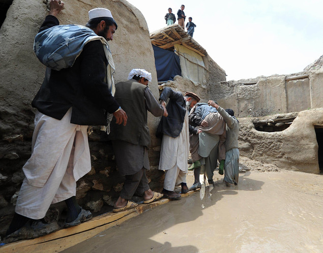 Afghan men rescue an elderly man after the flood