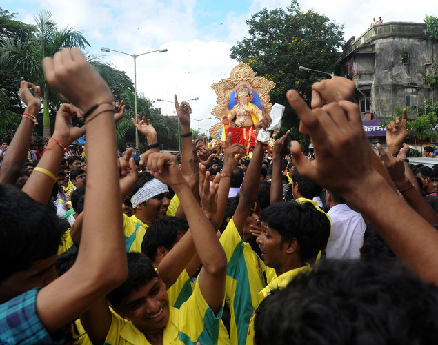 Indian Hindus dance to music as they carry a huge idol of the elephant-headed Hindu god Lord Ganesha through the busy streets of Mumbai.