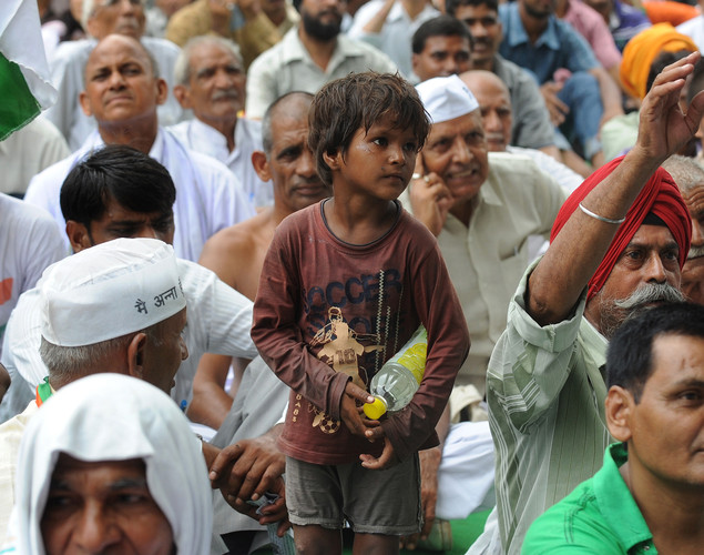 A homeless child stands amongst supporters of anti-corruption activist Anna Hazare during a protest in New Delhi.
