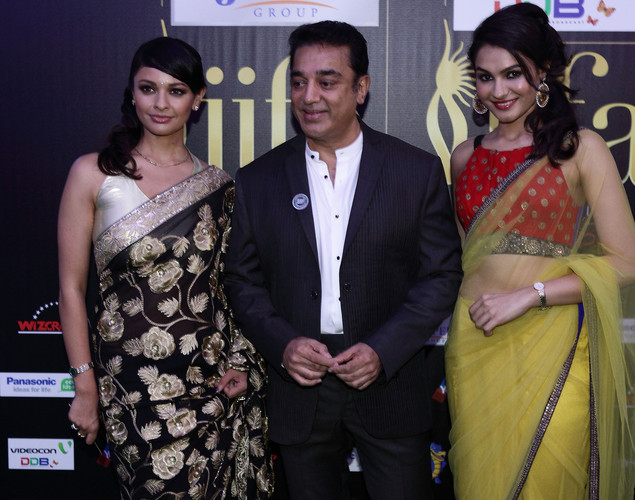 Indian actor Kamal Hassan (M) poses with Bollywood actresses Andrea Jeremiah (R) and Pooja Kumar at the IIFA green carpet event at the 2012 International India Film Academy Awards at the Singapore Indoor Stadium.