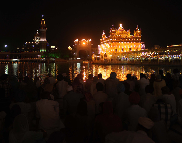 Indian Sikh devotees sit at the illuminated Golden Temple in Amritsar.