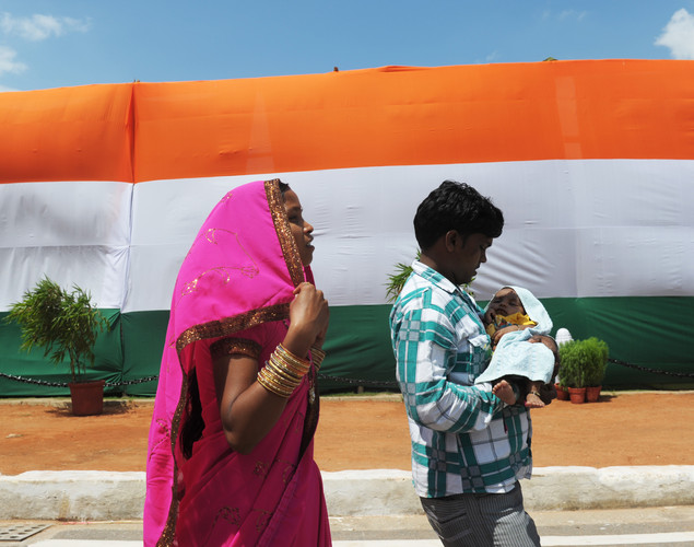 An Indian couple walk with their child past a huge Indian flag adorning the India Gate monument in New Delhi during Independence day celebrations on August 15, 2012.