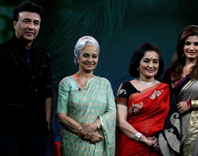 Waheeda Rehman (2L) and Asha Parekh (2R) pose onstage with music director Annu Malik (L) and show host Raveena Tandon (R) during the NDTV talk show 'Issi Ka Naam Zindagi' in Mumbai on April 19, 2012.