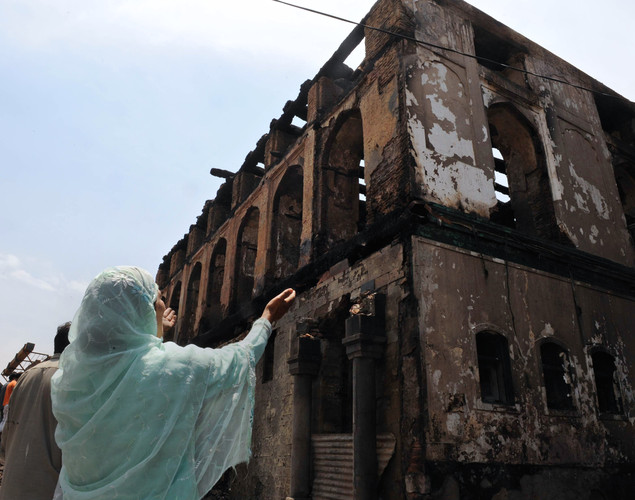 A Kashmiri Muslim woman grieves as unseen fire services personnel and volunteers clear debris from the charred remains of the 200-year old shrine of Sheikh Abdul Qadir Jeelani, also known as Dastigheer Sahib, in downtown Srinagar.