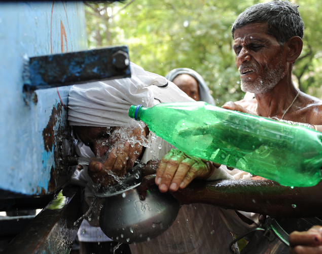 Protesting farmers collect drinking water from a water tanker on a hot summer day in New Delhi.