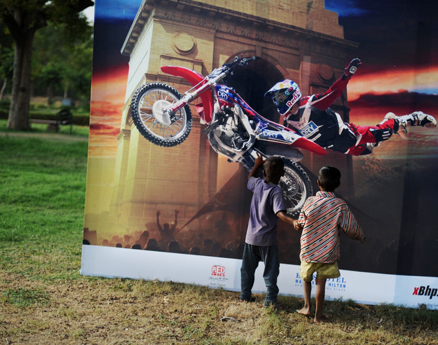 Two street children check out an image on a promotional banner announcing a motorcycle show near India Gate in New Delhi.