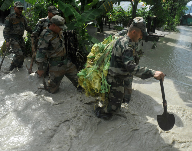 Indian army personal, carrying supplies to repair a damaged dam, wade through flood waters at Milanmore village on the outskirts of Siliguri.