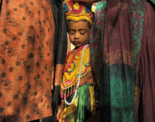A young Indian Hindu devotee dressed as the Hindu God Lord Krishna stands amidst his family members before a fancy dress competition held at the International Society for Krishna Consciousness (ISKCON) temple in Bangalore on August 9, 2012 on the eve of 'Krishna Janmashtami'.