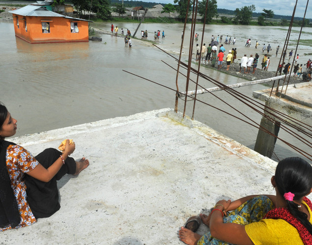 Indian residents sit on a rooftop as flood waters submerged their houses at Milanmore village on the outskirts of Siliguri.