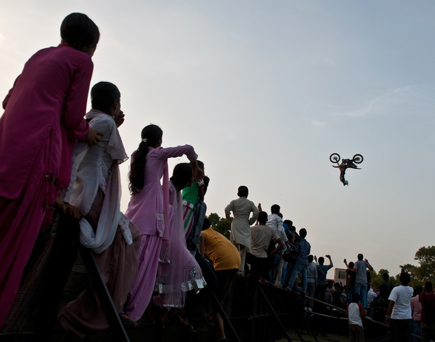 Indian spectators watch as a Freestyle Motocross (FMX) RedBull X-Fighters rider performs at the India Gate in New Delhi.