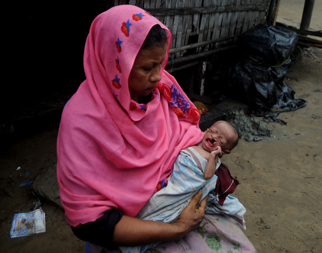 An abandoned baby girl from Myanmar, rescued from a boat by Bangladeshi border guards, is pictured with her Bangladeshi caregiver at a village in Teknaf.