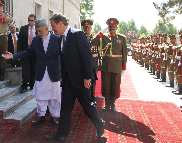 Afghan President Hamid Karzai (L) gestures to Britain's Prime Minister David Cameron after they inspected a guard of honour ceremony in Kabul.
