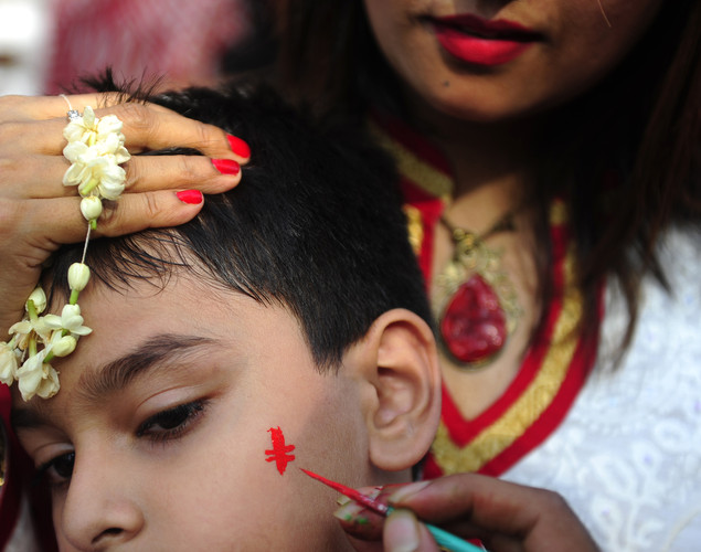 "A Bangladeshi artist paints a design on the face of a child during celebrations of the Bengali New Year or ""Pohela Boishakh"" in Dhaka."