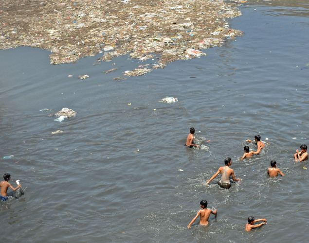 Pakistani youths cool off near floating trash in a polluted canal during a hot day in Rawalpindi.