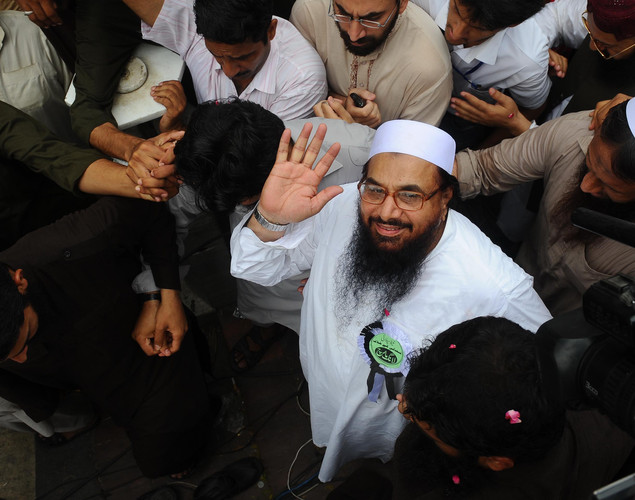 Hafiz Saeed, leader of Defense of Pakistan coalition waves as he arrives to attend a march in Lahore.