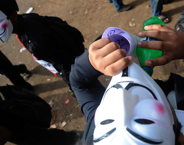 An activist supporting the group Anonymous wearing masks takes a drink during protest against the Indian Government's increasingly restrictive regulation of the internet in Mumbai.