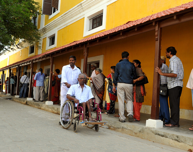 A physically challenged elderly Indo-French citizen (C) is transported on a wheelchair from a polling booth by an assistant in Pondicherry.