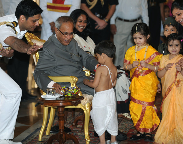 Indian President Pranab Mukherjee (2L) interacts with children after they tied a 'Rakhi' - Sacred Thread - onto his wrist at The Presidential Palace in New Delhi.