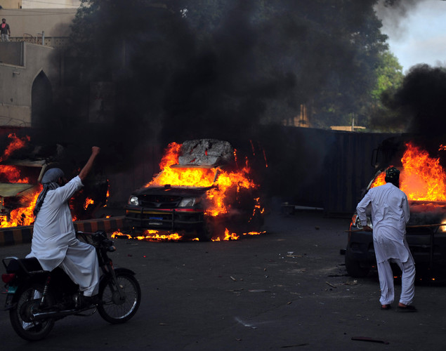 A Pakistani Muslim demonstrator (R) hits a burning police vehicle during a protest against an anti-Islam film in Karachi.