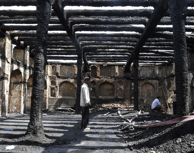 A Kashmiri Muslim looks on inside the charred remains of the 200-year old shrine of Sheikh Abdul Qadir Jeelani, also known as Dastigheer Sahib, in downtown Srinagar.