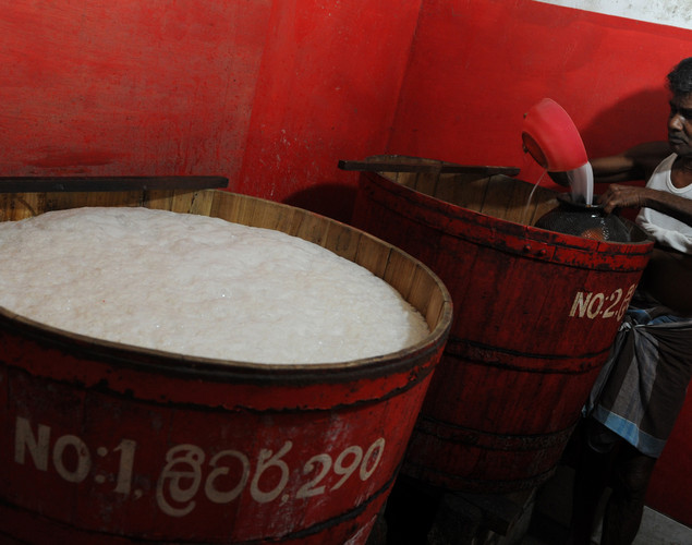 A toddy shop worker fills a vessel containing palm wine, or toddy as it is locally known, in Aluthgama.
