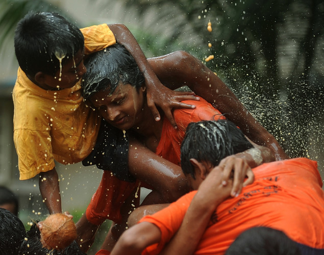 Indian visually impaired children hold onto each other as their human pyramid collapses while trying to break a dahi-handi, curd-pot, suspended in the air during a celebration at the Victoria School for the Blind in Mumbai on August 9, 2012, on the eve of 'Janmashtami' which marks the birth of Hindu God Lord Krishna.