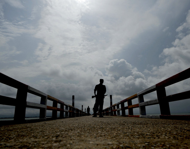 A Bangladeshi Border Guard keeps watch on a jetty on the Naf river in Teknaf.
