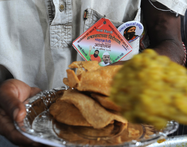Supporters of Indian yoga guru Baba Ramdev receive food during a protest in New Delhi.