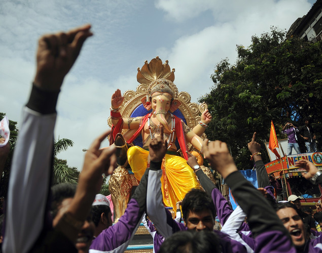 Indian Hindus dance as they carry a huge idol of the elephant-headed Hindu god Lord Ganesha through the streets of Mumbai.