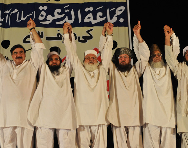 Leaders of the Defense of Pakistan coalition raise their hands in a show of solidarity during a protest rally in Islamabad against the reopening of NATO supply to Afghanistan.