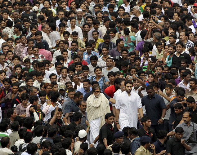 Bollywood superstar Amitabh Bachchan, center and his son actor Abhishek Bachchan, center right, walk through a sea of fans and mourners to attend the funeral of Rajesh Khanna in Mumbai.
