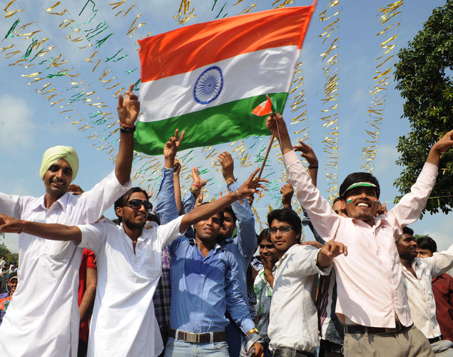 Indian revellers dance and wave national flags during a ceremony to celebrate India's Independence Day at the India-Pakistan Wagah border post on August 15, 2012.