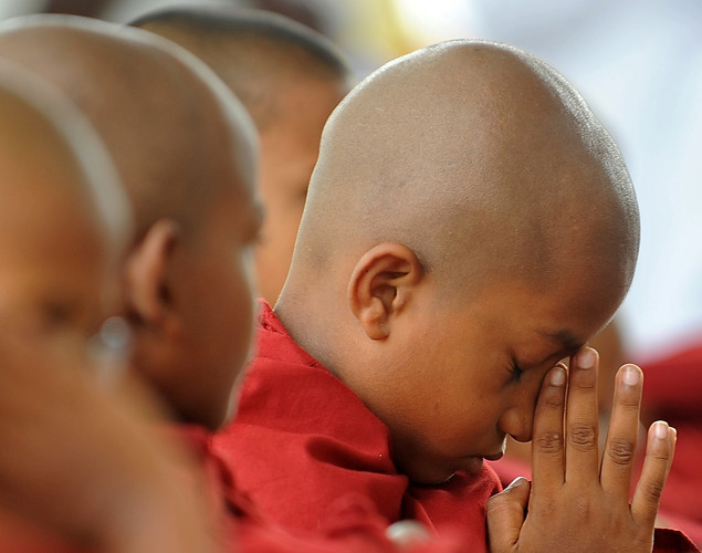 A young Sri Lankan Buddhist monk gestures during a morning walk for alms during the annual Buddhist festival of Vesakha in Colombo.