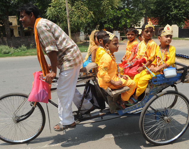 An Indian rickshaw driver transports children dressed as Hindu God Lord Krishna from school in Amritsar on August 9, 2012 on the eve of the 'Janmashtami' festival.
