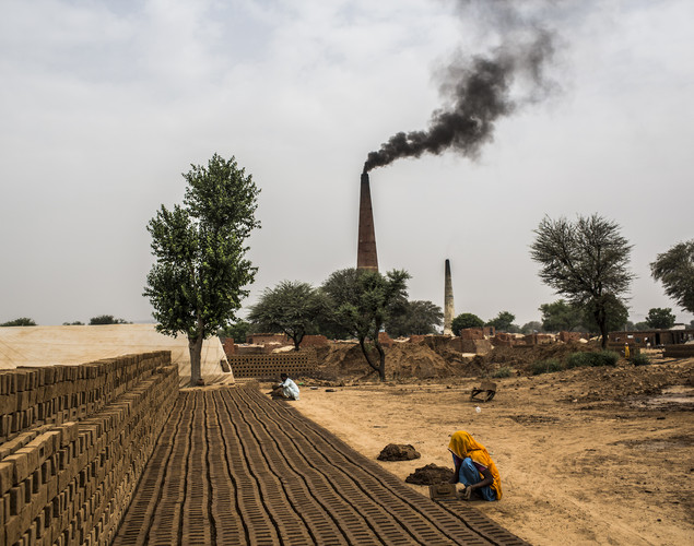 Laborers shape a mud-based mixture into bricks at a brick making facility on May 23, 2012 in a village near Jaipur, India.