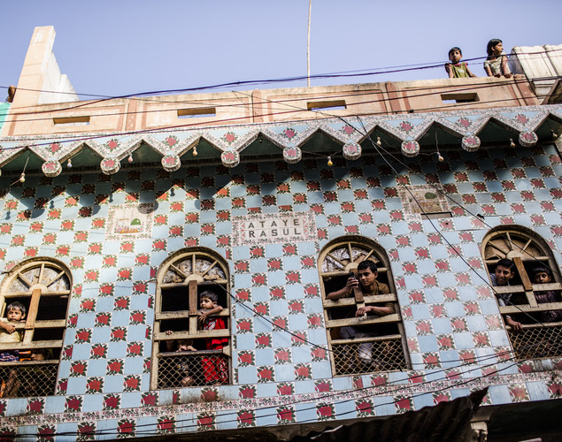 Children look out from windows as they watch Sufi Muslim devotees below during the annual 'Urs' Festival procession.