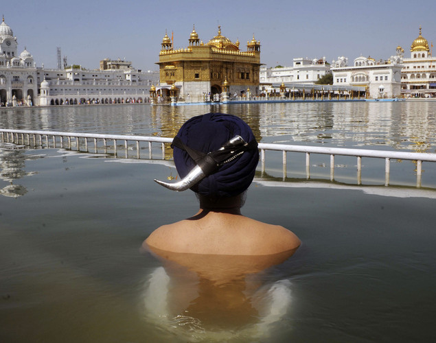 An Indian Sikh devotee takes a holy dip in the sarover (water tank) at the Sikh Shrine Golden Temple in Amritsar.