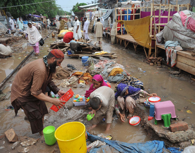 A Pakistani family salvages items from their stall at a flooded market area.