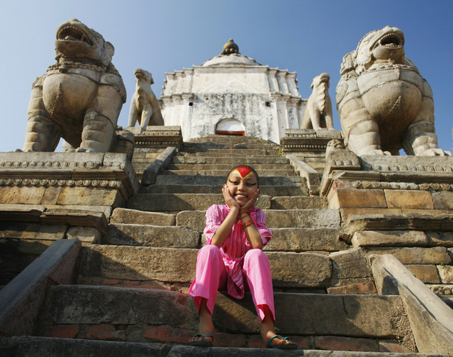 Kumari Devi (Royal Living Goddess) Sajani Shakya, 9, poses at a temple in Durbar Square on March 27, 2007 in Bhaktapur, Nepal. As a royal Kumari, Sajani has a very different life from the other two royal Kumari's, the rules in Bhaktapur differ and she is allowed to attend school and experiences a fairly normal life. Nepal has countless gods, goddesses, deities and Buddhas. The Kumari Devi is a young girl who is prepubescent, considered to be a real goddess, worshipped and revered, the practice going back hundreds of years into Nepali culture. She must meet 32 strict physical requirements ranging from the color of her eyes to the sound of her voice. Her horoscope must also be appropriate as well. Although there are many Kumaris in Nepal, the Kathmandu goddess is the most important and only makes rare public appearances. The Kumari's reign ends with her first period, after that she reverts back to the status of a normal mortal.