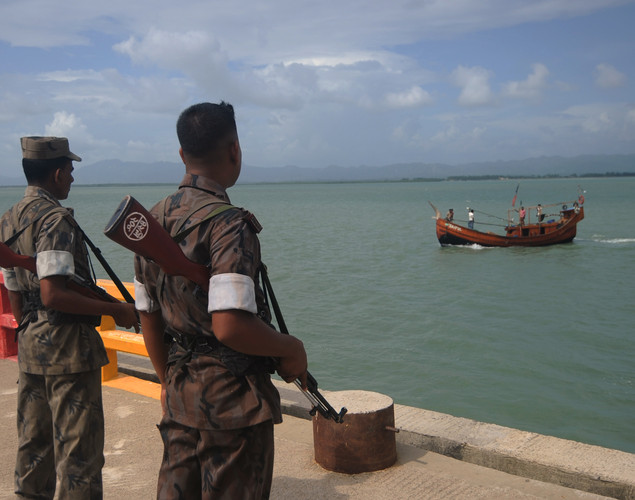 Bangladeshi Border Guard (BGB) personnel keep watch at a wharf in Taknaf on June 12, 2012, following the religious violence in neighbouring Myanmar.