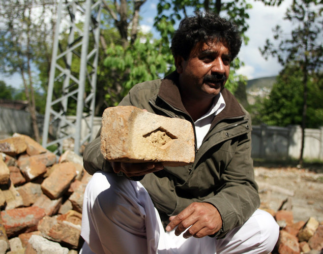 Shakeel Ahmad Yusufzai, a Pakistani contractor, displaying a brick from the demolished compound of slain Al-Qaeda leader Osama bin Laden, at his residence compound in northern Abbottabad.