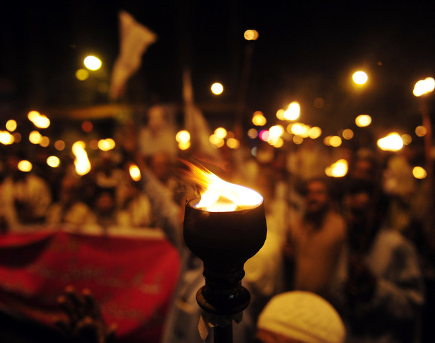 Pakistani labor union members carry lit torches as they march for better wages and conditions during a rally in Karachi.