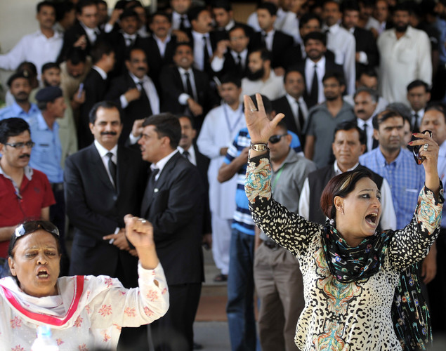 Activists of ruling Pakistan Peoples Party (PPP) shout slogans against the Supreme Court Chief Justice while anti-government lawyers (rear) are seen gathered following the verdict against Pakistan's Prime Minister Yousuf Raza Gilani out side the Supreme Court in Islamabad.